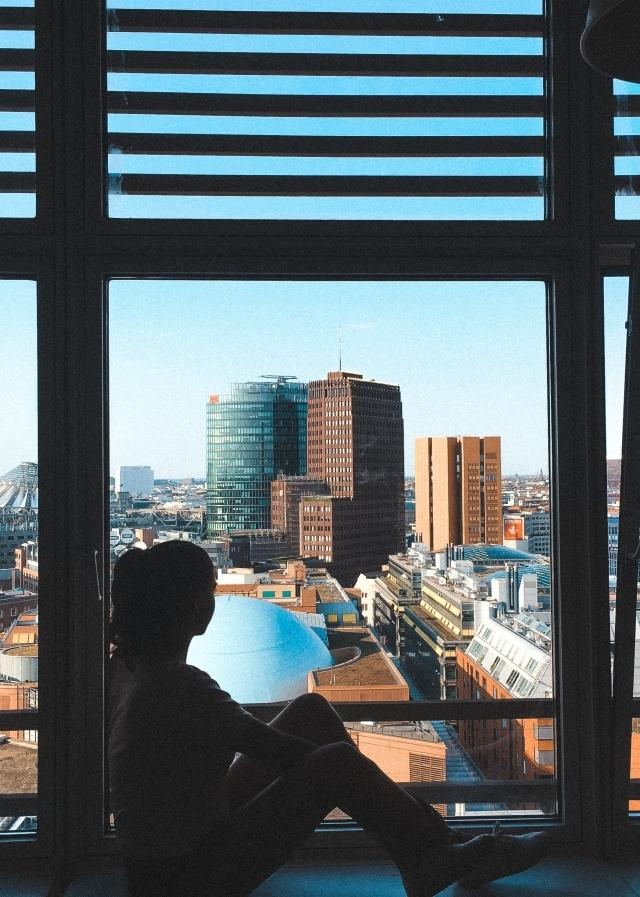 A girl is sitting inside of her window and looking out at the city.