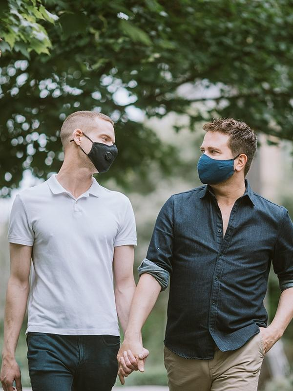 A male couple walks outdoors wearing masks