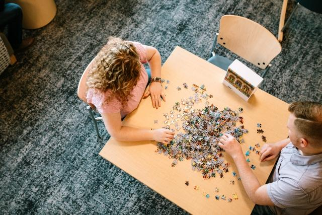 Patients put together a puzzle in a treatment center common area