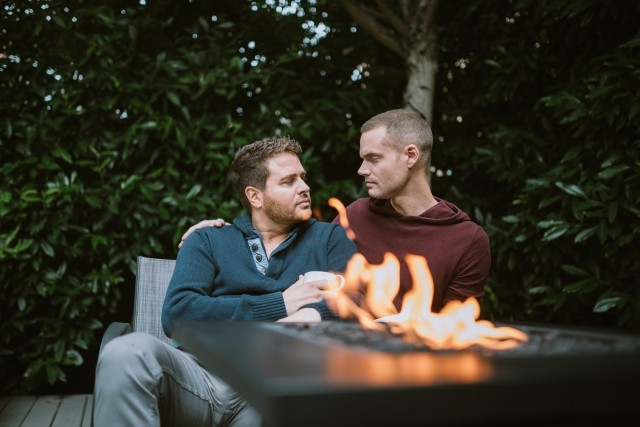 Male couple chatting by outdoor fire