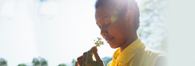 Young woman smells a flower in the sunlight