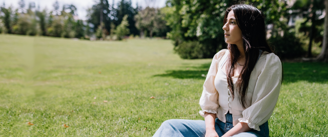 A woman sits outdoors on the grass in a park