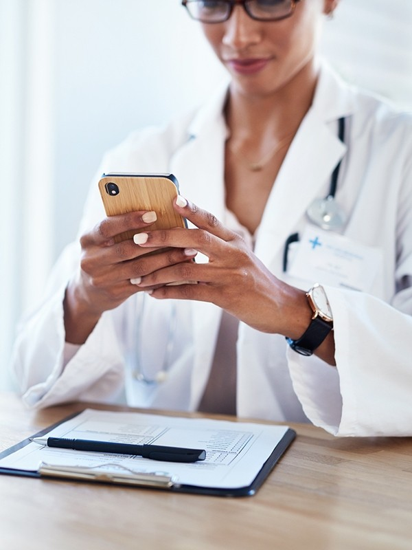A doctor looks at an app on a cell phone