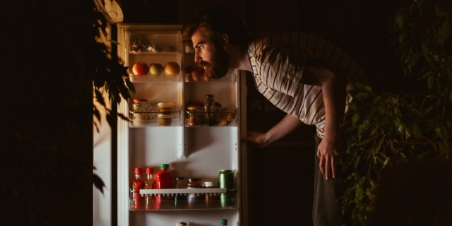A man looks in a refrigerator at night