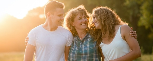 A family standing outdoors at sunset