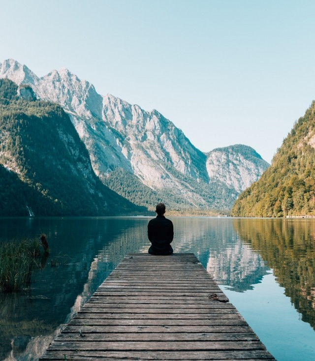 A person is sitting on a boat dock in the mountains.
