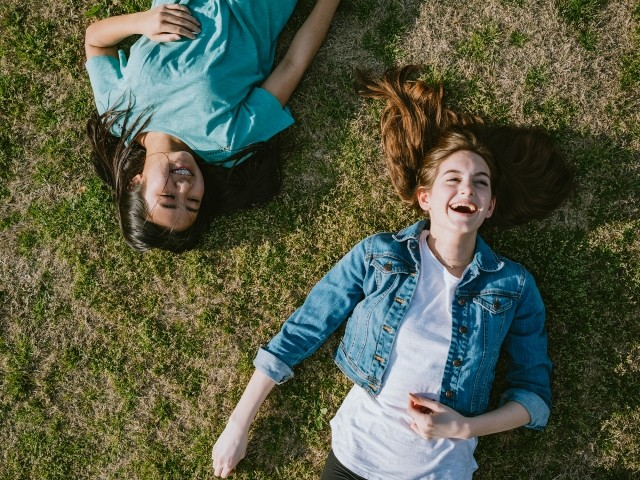 Two young women lay in the grass