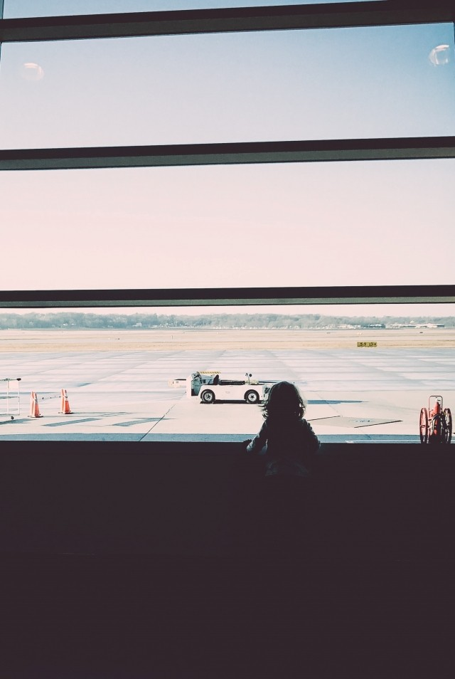A young girl is looking out the window at the airport