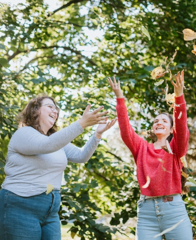 Two young women are throwing leaves in the air