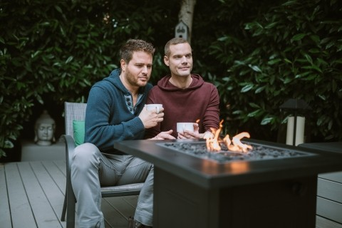 Gay couple sitting by outdoor fire
