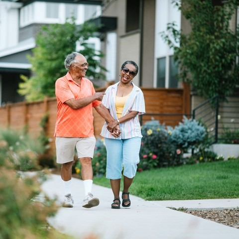 An older couple walks outdoors in their neighborhood