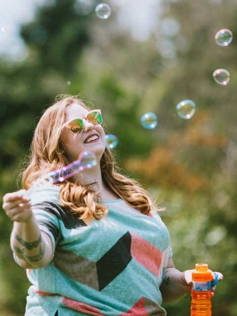 A woman blows bubbles in a park
