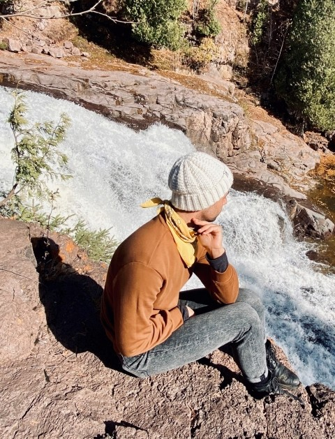 Eric Dorsa is sitting near a river in the mountains