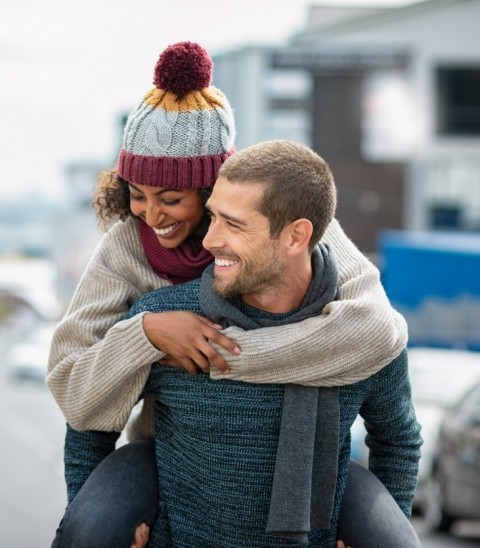 A woman is hugging a man as they pose for a photo