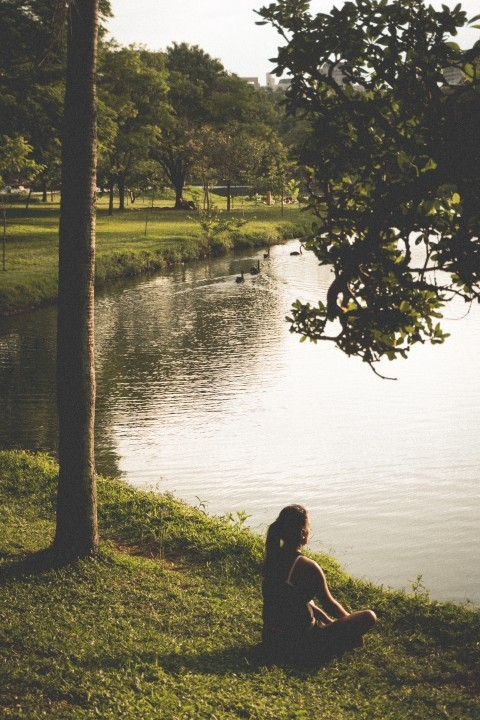 A woman is sitting at a lake in the park